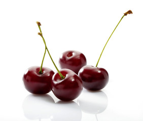 Four cherries close-up on white background with reflection