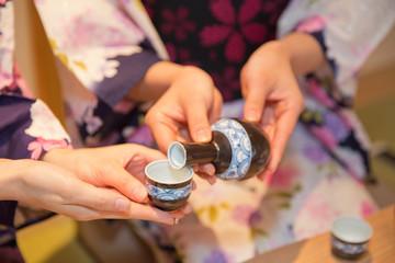 日本酒を注ぐ浴衣姿の女性2人の手