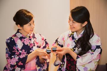 日本酒で乾杯する浴衣姿の若い女性2人