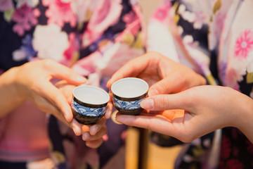 日本酒で乾杯する浴衣姿の女性2人の手