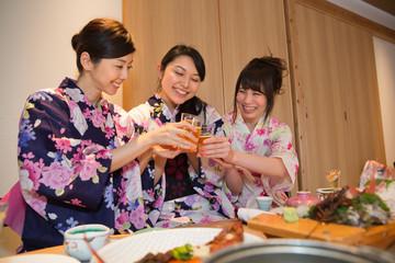 ビールで乾杯する浴衣姿の若い女性3人