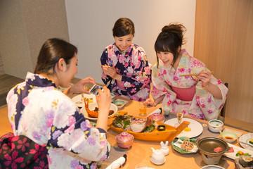 旅館の食事をスマホで撮影する女性3人