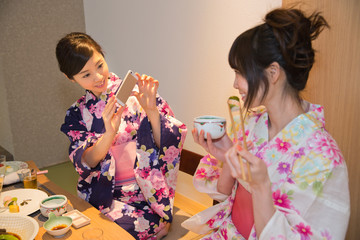 旅館の食事中にスマホで撮影する女性2人