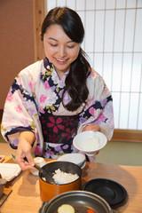 ご飯を盛り付ける浴衣姿の若い女性