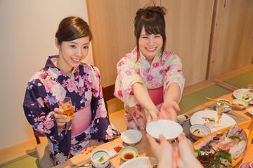 茶碗を受け取る浴衣姿の若い女性