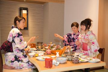 旅館の食事を食べる浴衣姿の若い女性3人