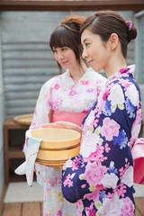 風呂桶を持って立つ浴衣姿の若い女性2人