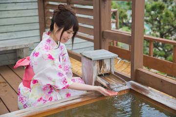 露天風呂の湯に手を入れる浴衣姿の若い女性