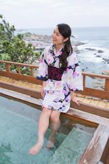 露天風呂で足湯を楽しむ浴衣姿の若い女性