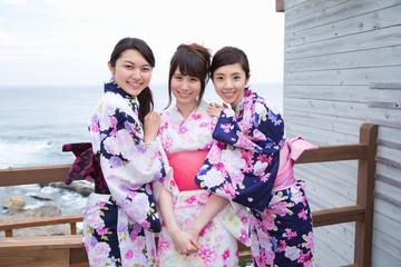 浴衣姿でベランダに立つ若い女性3人