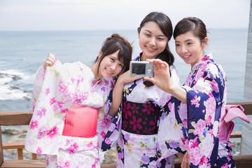 浴衣姿でデジカメで写真を撮る若い女性3人