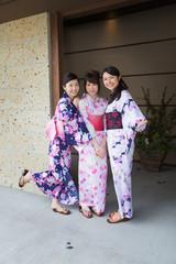 浴衣姿で旅館の玄関に立つ若い女性3人
