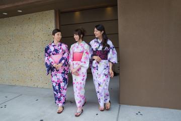 浴衣姿で旅館の中を歩く若い女性3人