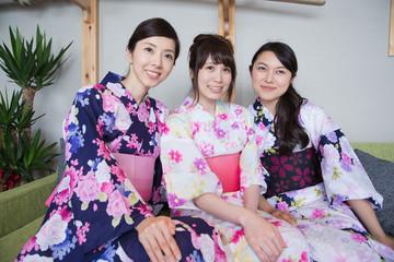 浴衣姿で旅館の中でくつろぐ若い女性3人