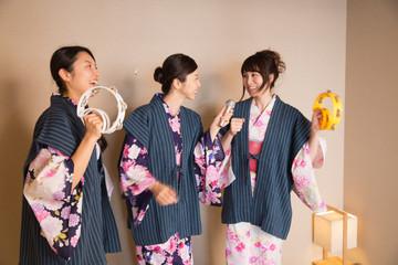 浴衣姿でカラオケを楽しむ若い女性3人