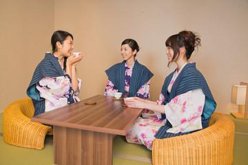 浴衣姿で旅館の客室でくつろぐ若い女性3人