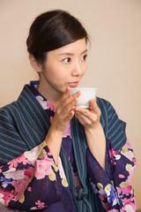 浴衣姿でお茶を飲む若い女性