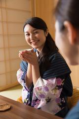浴衣姿で旅館の客室でくつろぐ若い女性2人