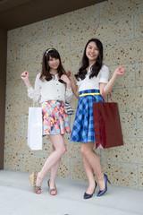 買物袋を持って立つ若い女性2人