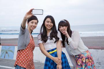 海岸でスマホで写真を撮る若い女性3人