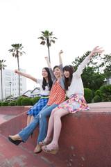 遊歩道の端に座る若い女性3人