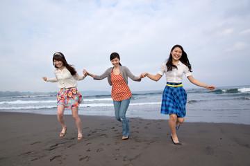 砂浜を手を繋いで走る若い女性3人