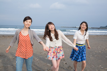 砂浜を手を繋いで歩く若い女性3人