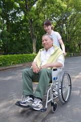 シニア男性の車いすを押す介護福祉士