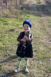 girl in a beret smiles with a kitten on his hands