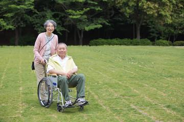 シニア男性の車いすを押すシニア女性