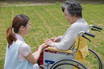 車いすに乗るシニアの手に触れる介護福祉士