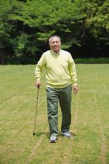 杖をついて歩くシニア男性