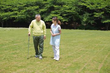 シニア男性の歩行を介助する介護福祉士