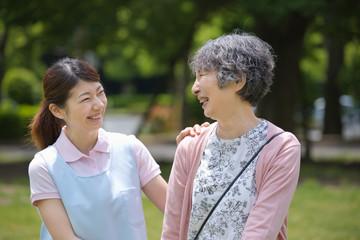 シニア女性の肩に手を置く介護福祉士