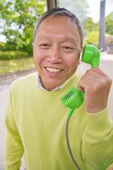 公衆電話で電話をかけるシニア男性