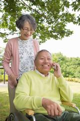 公園でスマートフォンで話す老夫婦