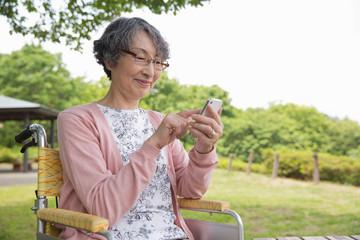 公園でスマートフォンを使用するシニア女性