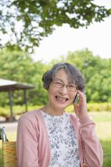 公園でスマートフォンで話すシニア女性