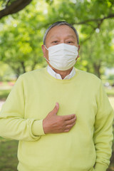 公園でマスクを着用しているシニア男性