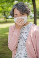 公園でマスクを着用しているシニア女性