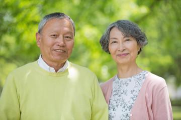 公園で並んで立つ老夫婦