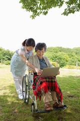 公園でパソコンを見るシニアと介護福祉士