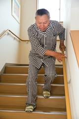 手すりに掴まって階段を下りるシニア男性