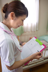 書類を見る看護師