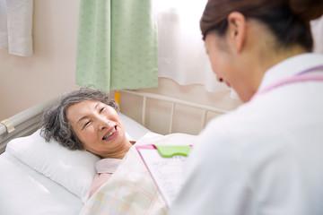 看護師と話すシニアの女性患者