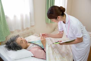 体温計を見るシニアの女性患者と看護師