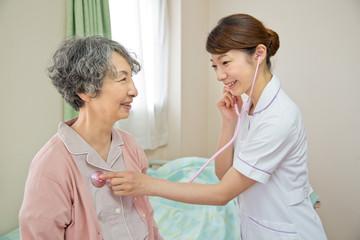 シニア女性患者に聴診器をあてる看護師