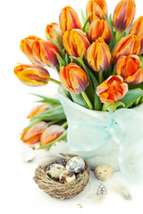 Easter concept, orange tulips and quail eggs in nest