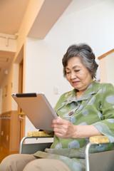 タブレット端末を操作するシニア女性患者