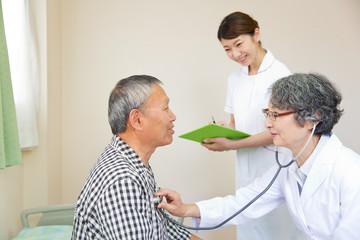 シニア男性患者を診察する医師と看護師